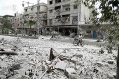 A Syrian man walks with a bicycle along a road that was destroyed in an air strike in the rebel-controlled town of Hamouria, in the eastern Ghouta region on the outskirts of the capital Damascus on...