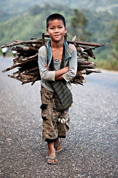 Boy with firewood, Laos. Children work all around the world; however, it's important to know the difference between children helping their family and children working at terrible jobs.