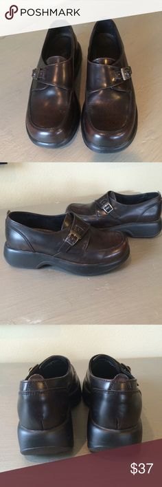 Dansko Dark Brown Buckle Clogs Loafers These are in very good pre-loved condition with only minor signs of wear to the leather. Loafer style clogs with a crossover buckle detail. These are labeled as a size 39. From the Dansko website, this fits a U.S. 8.5/9. Please know your UK size prior to purchasing. Dansko Shoes Mules & Clogs