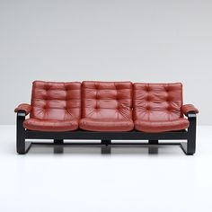 Here a nice comfortable 1970s red leather sofa supported on black wooden frame.