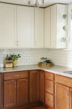 I'm in love with this Two tone kitchen reveal- White upper cabinets, darker wood base lowers, and subway tile backsplash