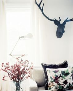 November 2012 Issue Photo - An iron stag head above a linen couch with floral pillows