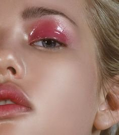 Glossy pink eye makeup paired with stained lips in a matching color and luminous glowing skin.