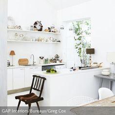 Obwohl die Küche in einem klaren Weiß gehalten ist, wirkt sie nicht kalt. Der Grund sind der antike Stuhl aus Holz, der Esstisch im Vintage-Look sowie die…