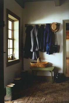 Farmhouse entry with peg coat rack and rustic bench.