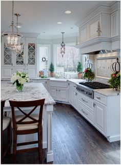 Well-Dressed Traditional Kitchen | Kitchen Inspiration | Traditional kitchen designed by Drury Design, using a soft white cabinet finish with pewter colored glazing, and Snow White granite countertops with a pencil edge. Pendant lights from Hudson Valley Lighting, polished nickel faucetry from Rohl, and refinished oak floor with custom stain color and wax finish.