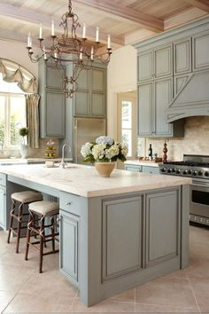 French style Kitchen- blue - green glazed cabinets, gorgeous Paris flea market style chandelier, thick stone counter tops-without very top shelf of cabinets
