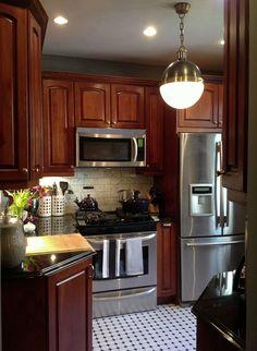 Cherry wood cabinets / Black white hexagon tiles / Hicks pendant / Marble backsplash / Granite countertops / Benjamin Moore Chelsea Gray / Kitchen design Apple a Day Beauty