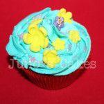 Cupcake de vainilla con frosting azul de fresa y flores de pasta de azucar