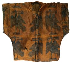 An important post-sasanian silk shirt, Khurasan or Central Asia, 7th-9th century the shirt opening to the front with a v-shaped collar and short sleeves, woven with cream, honey and blue silk threads, with a repeat pattern of confronting pheasants each clasping a pearled disc or crown in its beak and standing on a stylised base