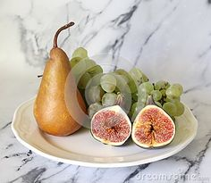 Grapes, figs, and a pear with marble background