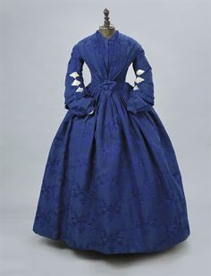 A ROYAL BLUE SILK DAMASK GOWN LATE 1850S EARLY 1860S One piece, the bodice pointed and with pleated detail to sloping shoulders, the bell sleeves with net insets ands with separate matching undersleeves and associated white gloves worked in blue-purple 25.5in. (64.7cm.) waist Christie's Auction House