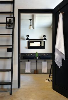 Black and white minimalist industrial style bathroom with black ladder flanking a black bathroom door accented with a copper towel rack. Timeless Bathroom, Eclectic Bathroom, Bathroom Styling, Modern Bathroom, Industrial Bathroom, Bathroom Doors, White Bathroom, Bathroom Ceilings, Black Bathrooms
