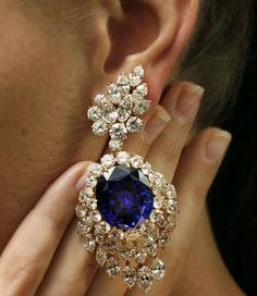A model from Christie's in Geneva displays a pair of earrings from Gerard consisting of a 52.72 carat sapphire and 49.84 carat diamonds.