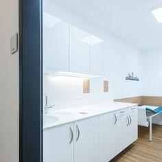 Diese Laborzeile in weiß hat zwei fugenlose Becken und einen Papierabwurf in die Himacs Arbeitsplatte eingelassen. Papiertücher sowie Seife und Desinfektionsmittel werden aus dem Boden des Hängeschrankes entnommen. In die Wand sind zwei Durchreichen für Proben integriert. Das Labor verfügt über eine Patientenliege sowie auf der anderen Seite des Raumes über einen großen Stauraumschrank und einen Arbeitsplatz. Kitchen Cabinets, Storage, Furniture, Home Decor, Trendy Tree, Countertop, Purse Storage, Decoration Home, Room Decor