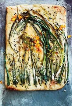 Onion & Wild Herb Flatbread  For the base, use a frozen pizza dough or make your favorite pizza or flatbread recipe. Before baking, place scallion, chives, or spring onion on top to resemble a wildflower bouquet or windblown grasses. Finish with marigold and fennel blossoms, good olive oil, and flaky black lava salt.
