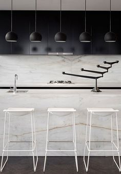 KITCHEN DESIGN IDEA: Marble splashbacks. Designed by Elenberg Fraser, Calacatta marble with prominent veins add subtle colour and texture to this stark black and white kitchen.