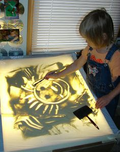 Light table- covered with white plastic bag and sand- super cool activity for kids