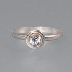 Modern style white sapphire engagement ring in sterling silver (also available in 14kt white gold) by Kryzia Kreations  http://www.kryziakreationsstudio.com/products/modern-white-sapphire-engagement-ring-in-sterling-silver  $165.00