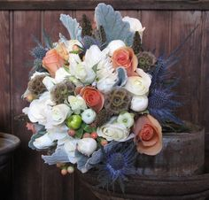 White, peach and blue wedding flowers including scabiosa pods, thistle, millet, roses, dahlias and dusty miller by floralartvt.com