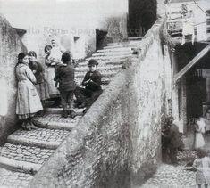 """Roma Sparita - """"Gruppo di ragazzi nel ghetto"""". L'immagine, che riprende un gruppo di ragazzi intenti a conversare tra loro, ci mostra anche le tipiche passerelle che univano le diverse abitazioni quali vie di collegamento in occasione delle alluvioni che frequentemente si verificavano nella zona."""