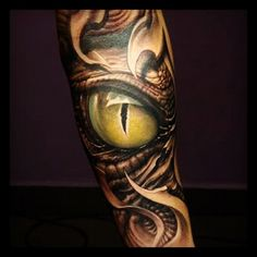lizard looking Eye Tattoo on leg.