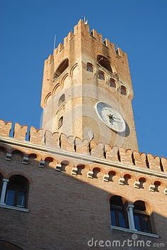 Photo made at a medieval palace in the center of Treviso in the Veneto (Italy). The picture shows the upper part, with the merlons, of the facade on which there are two pairs of windows separated by two white columns. Above the palace a large square tower with a clock rises in the blue sky.