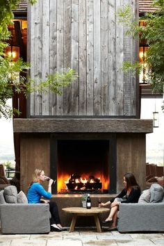 Amazing fireplace - love the height, how enormous it looks in the vaulted room with the texture of green plants/trees