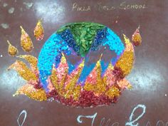 rangoli made out of bits of paper, flowers and glitter