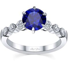 Blue sapphire engagement ring with round diamonds on the band.