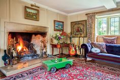 "This massive hearth in Lily Allen and husband Sam Cooper's English country estate is in the ""Gellybub"" room—a ""gentleman's room and is stacked with guitars, comfy armchairs, and shelves full of vinyl."""