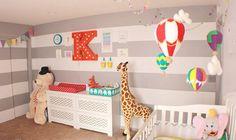 quarto de bebê decorado, parede de listras branco e cinza, bichos de pelúcia gigantes na decoração, móbile de balões coloridos em cima do berço