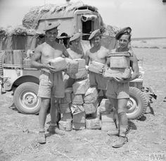 Men of 51st Highland Division show off their stock of cigarettes, 24 July 1943.