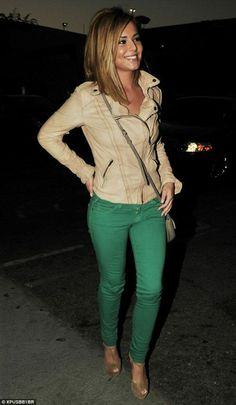 Beige leather jacket and green skinny jeans.