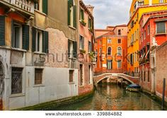 Colorful narrow lateral canal and pedestrian bridge in Venice with docked boats, Italy