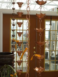 """Rain Chains are a beautiful and functional alternative to traditional metal and plastic closed gutter downspouts. Rain water is guided down the rain chains in an """"open"""" water flow system in a stunning display. Rain Chimes, Copper Gutters, Wood Shingles, Wall Lights, Ceiling Lights, Roofing Contractors, Roofing Materials, Roof Repair, Metal Roof"""