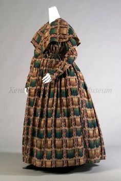 """1840-1849 Maternity dress and pelerine; cotton printed in dark green, brown, tan, blue and red plaid. Dress, high neck, open front, drawstring high waist, slim sleeves, full skirt. Self pelerine.  """"During pregnancy, women could wear less structured garments for leisure at home. However, boning and corsetry were expected outside the home. This dress, gathered with drawstrings in both bodice and skirt, accommodated the changing body.""""  Via Kent State University Museum."""