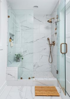 A teak bath mat sits on marble-like floor tiles in front of a walk-in shower boasting a glass door with a brushed gold handle. Bathroom Design Small, Bathroom Layout, Bathroom Interior Design, Modern Bathroom, Bathroom Shower Designs, Tile For Small Bathroom, Minimalist Small Bathrooms, Tile Walk In Shower, Best Bathroom Tiles