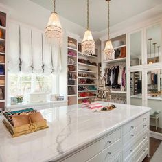 A beautiful feminine mirror door cabinets and white shelves display a collection of clothing, accessories, and shoes. A bright white space with exquisite beaded lighting, silk window treatment, and marble countertops is the perfect backdrop for an array of clothing, while remaining practical enough for everyday use.