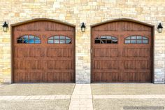 Stone Brick Home Featuring Two Car Dark Wood Garage Doors With Height  Window Panels.