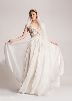 A luxurious silk georgette gown with a light crepe feel, elegant flowing silhouette, capped sleeve and beautiful open back. Cinched at the waist this exquisite gown features floral motifs and hand crafted organza flowers with delicate crystals hand sticthed in the center.