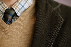 Camel sweater, navy striped neck tie, dark green corduroy blazer, blue, tan and white plaid shirt