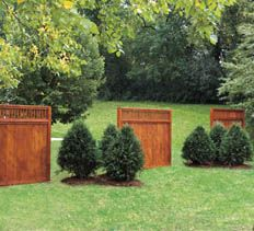 Instead of a full-length fence, consider creating a softer, more aesthetically pleasing divider consisting of three cedar panels and small groups of evergreen trees. The result is a lovely landscape element that also promotes privacy.