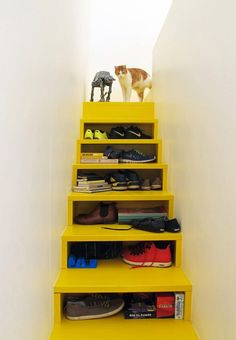 A yellow staircase leads to the lounging platform above, and features storage built into its treads.