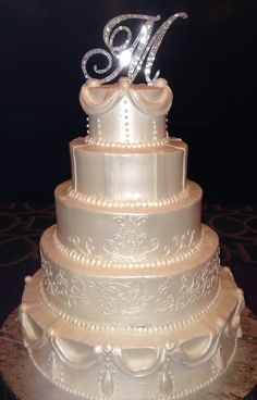 Tammy Allen Premier Wedding Cakes - Houston Cakes -  Five-tier wedding cake with pearlescent fondant frosting and elegant piped design with glittery monogram topper