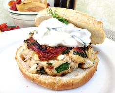 Recipe for moist turkey burgers stuffed with feta, spinach and sun-dried tomatoes and topped with tzatziki.