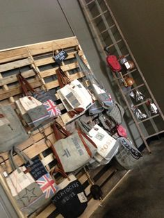 Updated:  Pallet Wall Retail Handbag Display! Added Branch Wall Coat Hooks to pallets for a great handbag display wall. Framed 4 pallets with 1x2 boards.  Great idea!