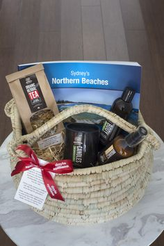 Thrive Promotional Products & Corporate Gifts - Client hamper project - fair trade basket, a lovely picture book, organic tea and beautiful candle and collection of hand and body creams.