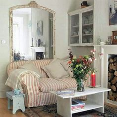 I love this juxtaposition of a small love seat overlapping a dramatic mirror in a small living space.