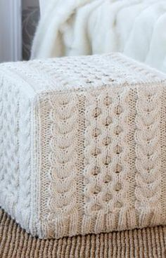 Cabled Ottoman Cover Knitting Pattern - Purchase an inexpensive ottoman cube and knit this gorgeous Aran knit cover for it. It looks great in white, but would look equally as attractive in whatever accent color you'd like!